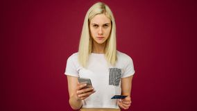 A young woman holds a smartphone and a credit card in her hands. Problems with a bank card, because of blocking or incorrectly. Entered pincode. Communication stock photography
