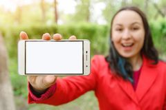 A young woman holds a smartphone with an empty white screen in front of her hand. With a place to mine space. Outdoors, in summer. On a Sunny day stock photography