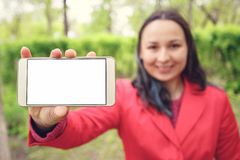 A young woman holds a smartphone with an empty white screen in front of her hand. With a place to mine space. Outdoors, in summer stock image