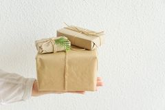 Young woman holds on stretched hand gift boxes wrapped in craft paper tied with twine. White background. Christmas New Years. Young woman holds on stretched hand stock images