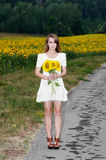 Young woman holds sunflowers Royalty Free Stock Photos