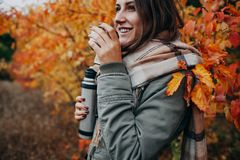 Young woman drinks tea in autumn forest royalty free stock image