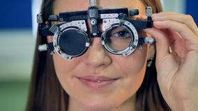 A young woman holds a trial frame during the lenses replacement. A woman confirms her results during an eye test with a trial frame stock video footage