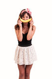 Young woman holds up banana to her mouth, imitating a smile on Stock Photo