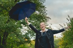 A young woman holds up her umbrella and cheers royalty free stock photography