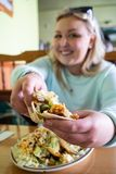 Young woman holds up a tasty taco at a Mexican restaurant, showing her delicious dinner. Woman is intentionally defocused to focus royalty free stock photography