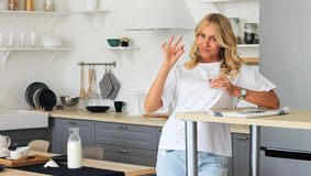 Woman holds vitamin`s pill and glass of water on the house kitchen stock images
