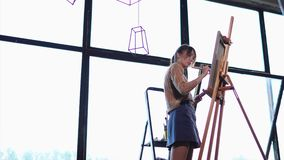 Young woman paints oil paints background on canvas, which stands on an easel. A young woman holds a wide brush in her hand to create a background in the picture stock footage