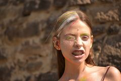 Young woman at Holi paint party. Young woman grin teeth at Holi paint party royalty free stock image