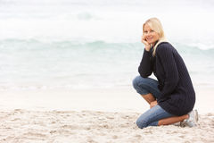Young Woman On Holiday Kneeling On Beach Stock Image