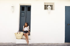 Young woman on holiday sitting on steps looking at her phone Royalty Free Stock Photos