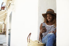Young woman on holiday sitting on steps looking at phone Stock Image
