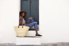 Young woman on holiday sitting on steps, looking to camera Stock Image