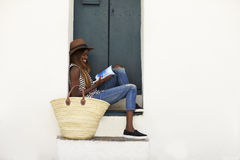 Young woman on holiday sitting on steps reading a guidebook Royalty Free Stock Photo