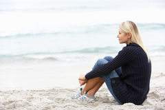 Young Woman On Holiday Sitting On Winter Beach. Looking At Shore Royalty Free Stock Images