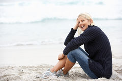 Young Woman On Holiday Sitting On Winter Beach. Smiling Stock Images