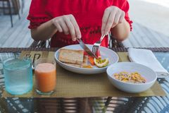 Young woman on holiday in a tropical island eating a healthy breakfast royalty free stock photography