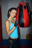 Young woman holding a punch ball at the gym. Fit young woman working out on a boxing bag Stock Image