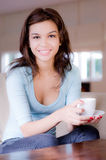 Young Woman At Home. A young woman at home on sofa holding cup and saucer stock images