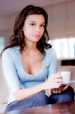 Young Woman At Home. A young woman at home on sofa holding cup and saucer royalty free stock photography