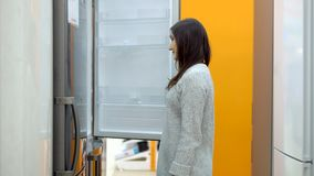 Young woman in a home appliance shop chooses a refrigerator royalty free stock photography