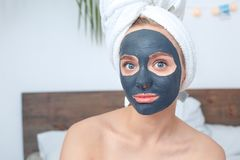 Young woman at home beauty care sitting with a mask on face looking camera excited close-up stock photography