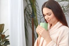 Young woman at home beauty care standing drinking hot tea closed eyes relaxed. Young woman rest at home beauty care standing holding cup drinking hot tea closed stock images