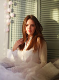 Young woman at home on bed in sunlight from window Royalty Free Stock Photography