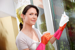 Young woman at home is cleaning a window. Young woman is cleaning a window royalty free stock photos