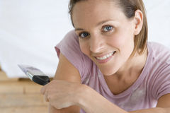 Young woman home decorating indoors with paintbrush, smiling, portrait, close-up,. Young women home decorating indoors with paintbrush, smiling, portrait, close stock photo