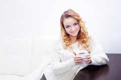 Young woman at home drinking hot coffee, wrapped Royalty Free Stock Photos