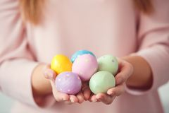 Young woman at home easter celbration concept in a bunny ears holding colorful eggs close-up stock photo