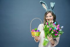 Young woman at home easter celbration concept in a bunny ears holding decorative eggs on sticks and buquet of tulips stock photos