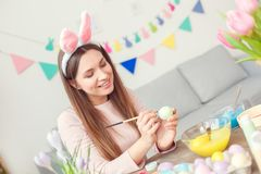 Young woman at home easter celbration concept in a bunny ears sitting coloring eggs painting picture with brush stock image