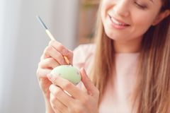Young woman at home easter celbration concept sitting coloring eggs making dots close-up royalty free stock photo