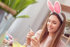 Young woman at home easter celbration concept in a bunny ears sitting coloring eggs painting dots royalty free stock photo