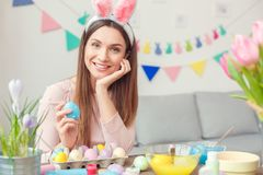Young woman at home easter celbration concept in a bunny ears sitting looking camera smiling royalty free stock images