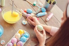 Young woman at home easter celbration concept back view sitting coloring eggs dipping brush in paint. Young woman at home easter celbration preparation concept Stock Photos