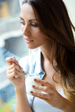 Young woman at home eating yogurt Stock Images