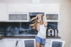 Young woman at home with headphones and home clothes dancing to stock image