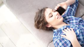 Young woman at home in the living room lying on coach smartphone communication close-up. Young woman at home in the living room lying on coach smartphone stock video