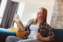 Young woman at home in the living room sitting on the coach reading story drinking tea stock image
