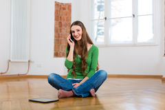 Young woman at home on the phone Stock Photo
