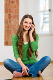 Young woman at home on the phone Stock Image