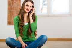 Young woman at home on the phone Royalty Free Stock Image