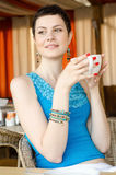 Young woman at home sipping tea from a cup Royalty Free Stock Images