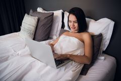 Young woman at home sitting on bed woke up browsing laptop royalty free stock image