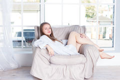 Young woman at home sitting on modern chair Royalty Free Stock Image