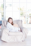 Young woman at home sitting on modern chair Stock Photography