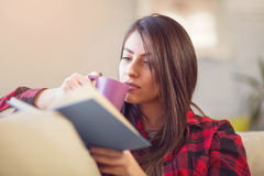 Young woman at home sitting on sofa relaxing reading book Royalty Free Stock Photography